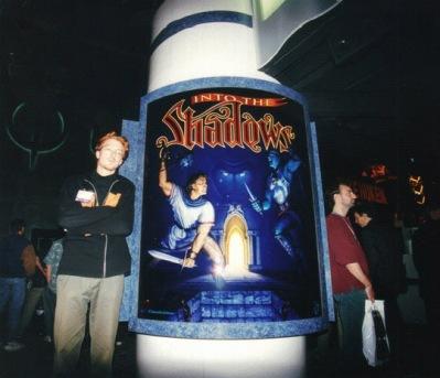 Jesper Kyd poserar bredvid en Into the Shadow-poster.